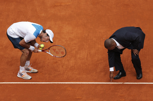 Juan Monaco from Argentina, left, discusses a point with umpire Carlos Bernardes during a Madrid Open tennis tournament match against Rafael Nadal from Spain in Madrid, Spain, Wednesday, May 7, 2014. (AP Photo/Andres Kudacki)
