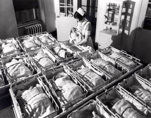 FILE - In this 1930 file photo, a nurse holds a baby in the nursery of the Pennsylvania Hospital in Philadelphia. Five years after the deepest global recession since the 1930s sent birth rates plunging around the world, many couples are still not having children. That's good news if you're worried about an overcrowded planet. But it's bad for the economy.  (AP Photo/File)