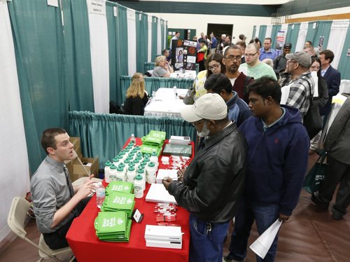 In this April 22, 2014 photo, Bryan Preston of Hannaford supermarkets, left, talks with job seekers during a job fair at Columbia-Greene Community College in Hudson, N.Y. The Labor Department reports the number of people who applied for unemployment benefits last week on Thursday, May 8, 2014. (AP Photo/Mike Groll)