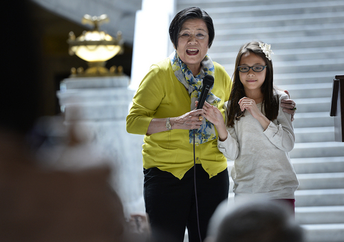 Scott Sommerdorf   |  The Salt Lake Tribune Margaret Yee, left, a decendant of the Chinese workers who helped build the transcontinental railroad, proudly introduced her 9-year old granddaughter Ellie Smith who spoke in English and Mandarin about the importance of remembering and honoring history. Representatives from Utah Gov. Gary Herbert's office joined other elected officials, including visitors from China's Guandong Province to recognize and honor the role played by primarily Chinese laborers in constructing and completing America's first transcontinental railroad, Friday, May 9, 2014. The event is part of the official commemoration of the May 10, 1869, driving of the Golden Spike that marked the connection of the Union and Central Pacific Railroads at Promontory Point, Utah.