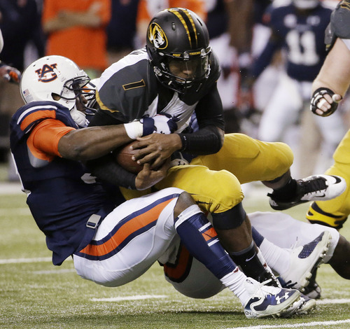 FILE - In this Dec. 7, 2013, file photo, Auburn defensive end Dee Ford tackles Missouri quarterback James Franklin (1) during the Southeastern Conference NCAA college football championship game in Atlanta. Ford and Chris Davis were much like their Auburn team early in the season, largely floating under the radar. The two defensive players garnered much more attention as the Tigers had success and are trying to forge NFL careers starting with the Senior Bowl. (AP Photo/David Goldman, File)
