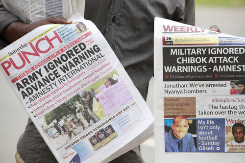Vendors sell local newspapers, with headlines stating the military was alerted four hours before abduction of Government secondary school Chibok girls  on a street in Abuja, Nigeria, Saturday, May 10, 2014. The weakness of the Nigerian armed forces was highlighted Friday in a report which said the military did not respond to warnings that Boko Haram rebels were about to attack Chibok, the town where the young women were abducted from their school. Nigerian security forces had four hours of notice about the April 15 attack by the rebels but did not react because of their fear of engaging the extremists, said Amnesty International, in a report citing multiple interviews with credible sources. (AP Photo/Sunday Alamba)