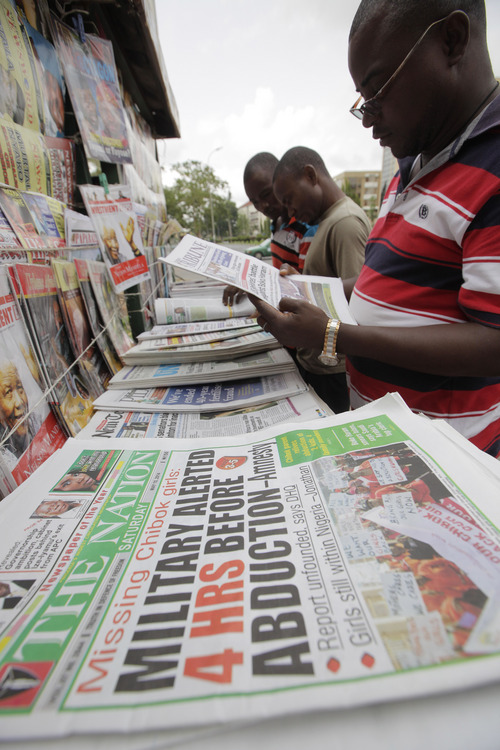 People read local newspapers, with headlines stating the military was alerted four hours before abduction of Government secondary school Chibok girls  on a street in Abuja, Nigeria, Saturday, May 10, 2014. The weakness of the Nigerian armed forces was highlighted Friday in a report which said the military did not respond to warnings that Boko Haram rebels were about to attack Chibok, the town where the young women were abducted from their school. Nigerian security forces had four hours of notice about the April 15 attack by the rebels but did not react because of their fear of engaging the extremists, said Amnesty International, in a report citing multiple interviews with credible sources. (AP Photo/Sunday Alamba)