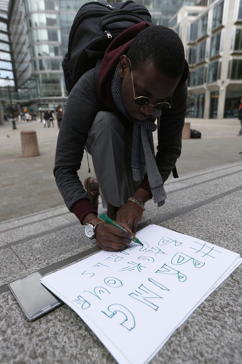 Nigerian student Caleb Udeoha writes out a placard in support of the campaign for the release of the kidnapped girls in Nigeria, outside Westminster Cathedral in London , Saturday, May 10, 2014. Global outrage against the abduction of more than 200 Nigerian girls by Islamist militant sect Boko Haram as a social media campaign drew worldwide support.  (AP Photo/Sang Tan)