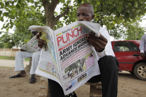 A man reads a local newspaper, with headlines stating the military was alerted four hours before abduction of Government secondary school Chibok girls  on a street in Abuja, Nigeria, Saturday, May 10, 2014. The weakness of the Nigerian armed forces was highlighted Friday in a report which said the military did not respond to warnings that Boko Haram rebels were about to attack Chibok, the town where the young women were abducted from their school. Nigerian security forces had four hours of notice about the April 15 attack by the rebels but did not react because of their fear of engaging the extremists, said Amnesty International, in a report citing multiple interviews with credible sources. (AP Photo/Sunday Alamba)