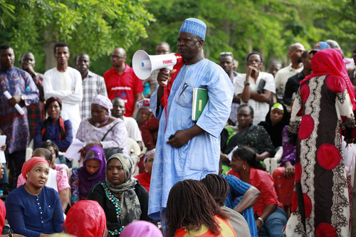 """Hosea Abana, centre, the chairman of the  Chibok community in Abuja, pauses, during a rally calling on the Government to rescue the school girls kidnapped from the Chibok Government secondary school, in Abuja, Nigeria, Saturday May 10, 2014. The president of Nigeria for weeks refused international help to search for more than 300 girls abducted from a school by Islamic extremists, one in a series of missteps that have led to growing international outrage against the government. The waiting has left parents in agony, especially since they fear some of their daughters have been forced into marriage with their abductors for a nominal bride price of $12. Boko Haram leader Abubakar Shekau called the girls slaves in a video this week and vowed to sell them. """"For a good 11 days, our daughters were sitting in one place,"""" said Enoch Mark, the anguished father of two girls abducted from the Chibok Government Girls Secondary School. """"They camped them near Chibok, not more than 30 kilometers, and no help in hand. For a good 11 days."""" (AP Photo/Sunday Alamba)"""