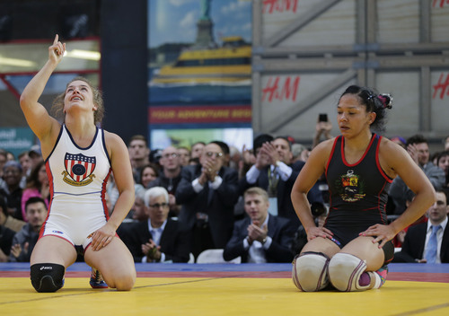 Helen Maroulis, left, of the United States, celebrates her win over Marcia Andrades, of Venezuela, after pinning her in the second period during an exhibition match at Times Square, Wednesday, May 7, 2014, in New York. Wrestlers competing in the exhibition included past and potential future Olympic athletes from the USA, Russia, Bulgaria, Venezuela and Canada. (AP Photo/Julie Jacobson)