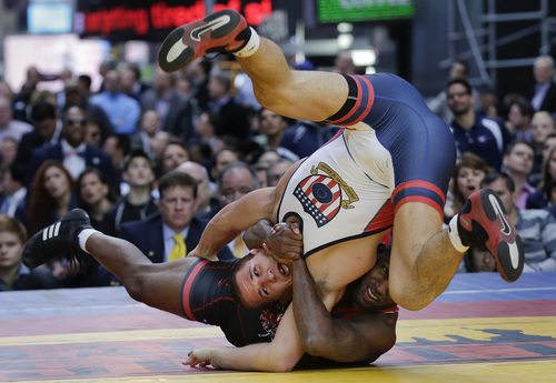 Canada's Haislan Garcia, right, takes down Logan Stieber of the United States during an exhibition wrestling match in Times Square, Wednesday, May 7, 2014, in New York. Wrestlers competing in the exhibition included past and potential future Olympic athletes from the USA, Russia, Bulgaria, Venezuela and Canada. (AP Photo/Julie Jacobson)