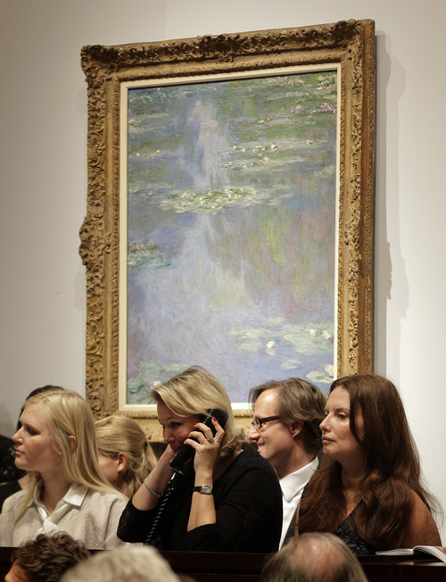 Bid takers receive bids over the phone under the Monet painting, Nympheas, during an impressionist and modern art auction at Christie's, Tuesday, May 6, 2014, in New York. The auction house says it expects to raise over $245 million from the sale of works including those by Monet, Renoir, Picasso, Degas, Matisse and Kandinsky. The painting sold for $24 million.  (AP Photo/Julie Jacobson)
