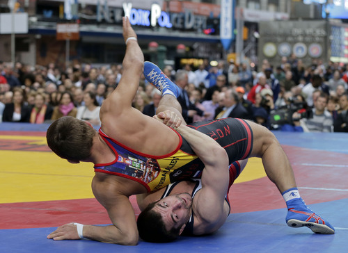 Brent Metcalf, of the United States, bottom takes down Russia's Magomed Kurbanaliev during an exhibition wrestling match, Wednesday, May 7, 2014, on Times Square in New York. Wrestlers competing in the exhibition included past and potential future Olympic athletes from the USA, Russia, Bulgaria, Venezuela, Spain and Canada. (AP Photo/Julie Jacobson) (AP Photo/Julie Jacobson)