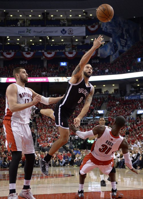 Toronto Raptors' Terrence Ross (31) fouls Brooklyn Nets' Deron Williams as Raptors' Jonas Valanciunas looks on during the second half of Game 7 of the opening-round NBA basketball playoff series in Toronto, Sunday, May 4, 2014. (AP Photo/The Canadian Press, Frank Gunn)