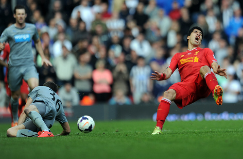 Liverpool's Luis Suarez, right, is fouled by Newcastle United's Paul Dummett during their English Premier League soccer match at Anfield in Liverpool, England, Sunday, May 11, 2014. (AP Photo/Clint Hughes)
