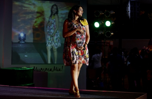 An expectant mother holds on to her belly as she pauses on the ramp during a fashion show organized to mark Mother's Day in Bangalore, India, Sunday, May 11, 2014. (AP Photo/Aijaz Rahi)