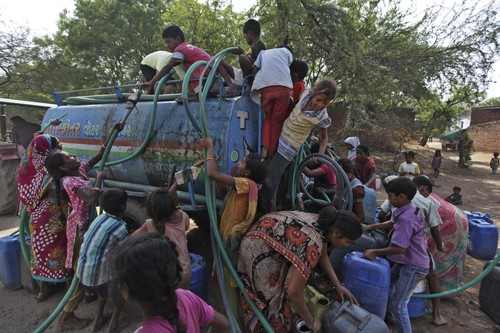 Indian women and children struggle to collect government-supplied water from a mobile tanker in Ramol, outskirts of Ahmadabad, India, Sunday, May 11, 2014. As India faces certain water scarcity and ecological decline, the country's main political parties campaigning for elections have all but ignored environmental issues seen as crucial to India's vast rural majority, policy analysts say. With 814 million eligible voters, India's weeks long general election runs through May 12, with results for the 543-seat lower house of Parliament set to be announced May 16. (AP Photo/Ajit Solanki)