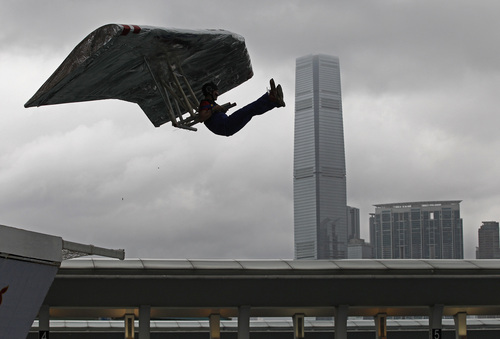 A participant sits in his self-made aircraft flying in front of the International Commerce Centre (ICC) at the Red Bull Flugtag (flight day) competition in Hong Kong, Sunday, May 11, 2014. Participants went into the air with home-made human-powered flying machines. (AP Photo/Vincent Yu)