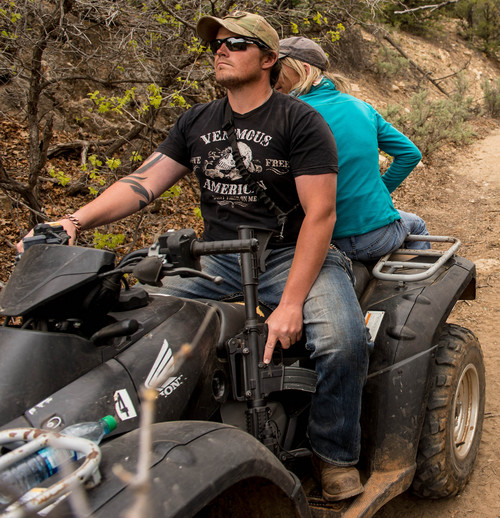 Trent Nelson  |  The Salt Lake Tribune A rider holds his finger off the trigger of his assault rifle as ATV riders make their way into Recapture Canyon, which has been closed to motorized use since 2007. The protest on Saturday, May 10, 2014 north of Blanding, came after a call-to-action by San Juan County Commissioner Phil Lyman.