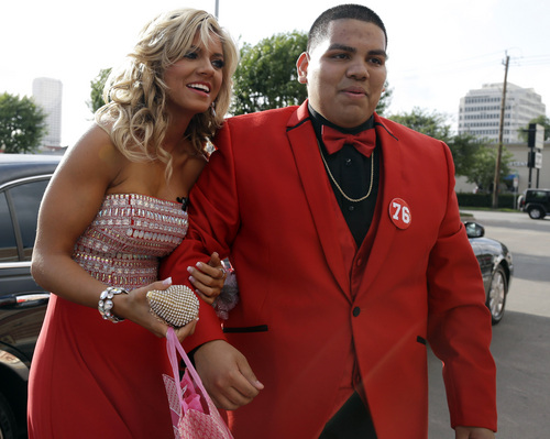 """High school student Michael Ramirez, right, and Houston Texans cheerleader Caitlyn pose for pictures outside a restaurant before attending the prom Saturday, May 10, 2014, in Houston. Ramirez sent Caitlyn a Twitter message saying """"If I get 10,000 retweets will you go to prom with me (insert smiley face.) you will get asked in a cute way!"""" He did and so she said yes. (AP Photo/Pat Sullivan)"""