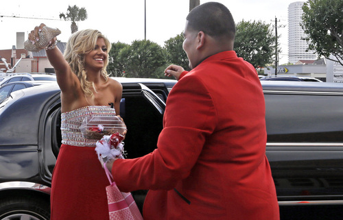 """High school student Michael Ramirez, right, and Houston Texans cheerleader Caitlyn meet outside a restaurant before attending the prom Saturday, May 10, 2014, in Houston. Ramirez sent Caitlyn a Twitter message saying """"If I get 10,000 retweets will you go to prom with me (insert smiley face.) you will get asked in a cute way!"""" He did and so she said yes. (AP Photo/Pat Sullivan)"""