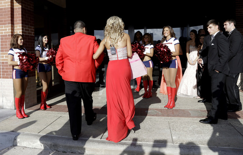 """Cameras, cheerleaders and friends meet high school student Michael Ramirez, center left, and Houston Texans cheerleader Caitlyn, wearing a mic battery pack on her back, at a restaurant before attending the prom Saturday, May 10, 2014, in Houston. Ramirez sent Caitlyn a Twitter message saying """"If I get 10,000 retweets will you go to prom with me (insert smiley face.) you will get asked in a cute way!"""" He did and so she said yes. (AP Photo/Pat Sullivan)"""