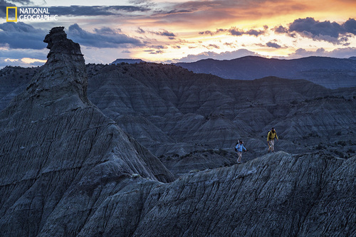 Photograph by Cory Richards On a cold May evening Sertich and volunteer Billy Doran walk a ridgeline -- often the only way to get from here to there in the fossil-rich badlands of southern Utah. Image from the May issue of National Geographic magazine. http://ngm.nationalgeographic.com/2014/05/utah-dinosaurs/richards-photography