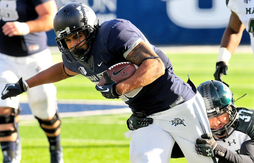 Utah State's Joey DeMartino (28) gets tackled by Hawaii's Charles Clay (37) during an NCAA college football game, Saturday, Nov. 2, 2013, in Logan, Utah. (AP Photo/Herald Journal, John Zsiray)