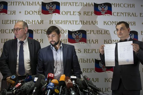 Co-chairman of the Presidium of the People's Republic of Donetsk Boris Litvinov, left, Insurgent leader head of the elections commission of the so-called Donetsk People's Republic Denis Pushilin, and vote-counter Roman Lyagin, right, show documents with the results of Sunday's referendum to journalists at a news conference in Donetsk, Ukraine, Monday, May 12, 2014.  The referendum balloting Sunday in the Donetsk and Luhansk regions, which together have 6.5 million people, was condemned as a sham and a violation of international law by Kiev's interim government and other western powers. (AP Photo/Alexander Zemlianichenko)