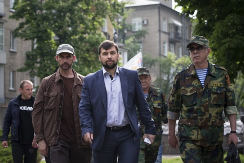 Insurgent leader Denis Pushilin, centre, walks with his bodyguards after his news conference in Donetsk, Ukraine, Monday, May 12, 2014.  The referendum balloting Sunday in the Donetsk and Luhansk regions, which together have 6.5 million people, was condemned as a sham and a violation of international law by Kiev's interim government and other western powers.  (AP Photo/Alexander Zemlianichenko)