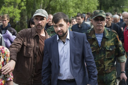 Insurgent leader Denis Pushilin, centre, walks through a crowd with his bodyguards after his news conference in Donetsk, Ukraine, Monday, May 12, 2014.  The referendum balloting Sunday in the Donetsk and Luhansk regions, which together have 6.5 million people, was condemned as a sham and a violation of international law by Kiev's interim government and other western powers. (AP Photo/Alexander Zemlianichenko)