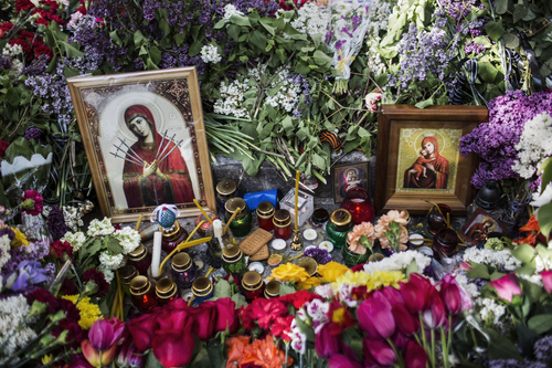In this photo taken on Sunday, May 11, 2014, flowers and Orthodox icons are seen outside a police station where a few people were killed during fighting between government forces and insurgents on Friday, May 9 in Mariupol, eastern Ukraine. The insurgents in the east have seized government buildings and clashed with government troops and police over the past month. More than 30 people have been reported killed since Ukrainian forces began trying to retake some eastern cities from the insurgents. (AP Photo/Manu Brabo)
