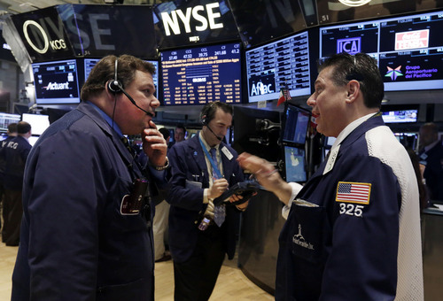 Traders John Santiago, left, and William McInerney, right, work on the floor of the New York Stock Exchange, Tuesday, May 13, 2014. The Standard & Poor's 500 index crossed above 1,900 for the first time Tuesday as investors assessed news on retail sales. DirecTV gained on reports that the AT&T is poised to buy the company for nearly $50 billion. (AP Photo)