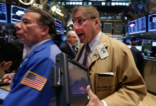Trader David Williams, right, works on the floor of the New York Stock Exchange Tuesday, May 13, 2014. The Standard & Poor's 500 index crossed above 1,900 for the first time Tuesday as investors assessed news on retail sales. DirecTV gained on reports that the AT&T is poised to buy the company for nearly $50 billion. (AP Photo)