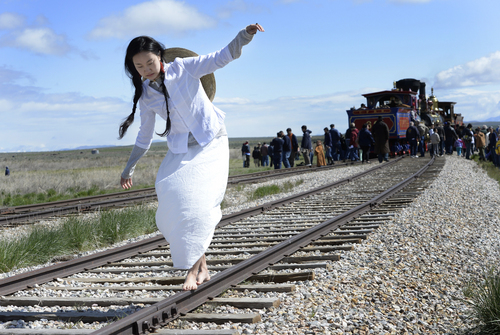 Scott Sommerdorf   |  The Salt Lake Tribune Dancer Wan Zhao walks along the tracks near the Golden Spike commemoration site. The Chinese community honored Chinese immigrants who built the railroad from the west by taking more than three busloads of people to the Golden Spike National Monument for the 145th commemoration of the completion of the transcontinental railroad, Saturday, May 10, 2014.