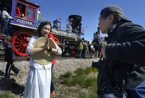 Scott Sommerdorf   |  The Salt Lake Tribune New York photographer Corky Lee, right, works with dancer Wan Zhao near one of the two locomotives used in the re-enactment of the Golden Spike ceremony, Saturday, May 10, 2014. The Chinese community honored Chinese immigrants who built the railroad from the west by taking more than three busloads of people to the Golden Spike National Monument for the 145th commemoration of the completion of the transcontinental railroad.