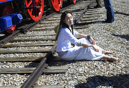Scott Sommerdorf   |  The Salt Lake Tribune Dancer Wan Zhao sits beside one of the railroad tracks that leads to the Golden Spike comemmoration ceremony, Saturday, May 10, 2014. The Chinese community honored Chinese immigrants who built the railroad from the west by taking more than three busloads of people to the Golden Spike National Monument for the 145th commemoration of the completion of the transcontinental railroad.