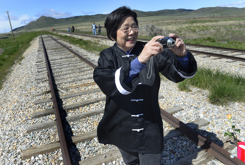 Scott Sommerdorf   |  The Salt Lake Tribune Margaret Yee, a decendant of Chinese laborers who built the transcontinental railroad makes a photo on the tracks near the Golden Spike commemoration ceremony, Saturday, May 10, 2014. The Chinese community honored Chinese immigrants who built the railroad from the west by taking more than three busloads of people to the Golden Spike National Monument for the 145th commemoration of the completion of the transcontinental railroad.