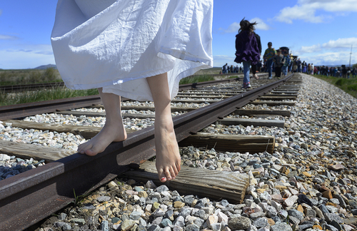 Scott Sommerdorf   |  The Salt Lake Tribune Dancer Wan Zhao walks down the track near the site of the Golden Spike re-enactment ceremony, Saturday, May 10, 2014. Zhao came to Utah to help the Chinese community honor Chinese immigrants who built the railroad from the west. She, and more than three busloads of people came to the Golden Spike National Monument for the 145th commemoration of the completion of the transcontinental railroad, Saturday, May 10, 2014.