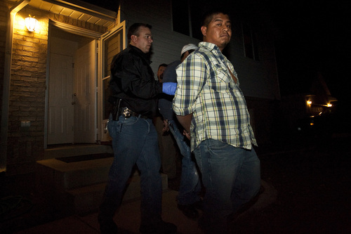 Chris Detrick | The Salt Lake Tribune  Utah Attorney General Special Agent Mick Spilker arrests two suspects at a home in West Point during a raid by the SECURE Strike Force. The collection of agents, funded by a federal grant, targets major crime inside Utah's undocumented immigrant population.
