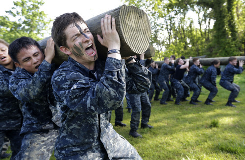 Phillip Metcalfe of Plano, Texas, screams as he lifts a log during Sea Trials, a day of physical and mental challenges for freshman midshipmen, known as plebes, that caps off their first year at the U.S. Naval Academy in Annapolis, Md., Tuesday, May 13, 2014. (AP Photo/Patrick Semansky)