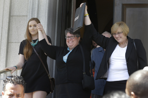 Plantiffs in the federal suit over Virginia's ban on gay marriage, Emily Schall-Townley, left, Carol Schall, center, and Mary Townley, raise their arms after a hearing on Virginia's same sex-marriage ban in Richmond, Va., Tuesday, May 13, 2014.  The 4th U.S. Circuit Court of Appeals in Richmond is taking up the issue of gay marriage, with arguments scheduled on a ruling that the state's ban on such unions is unconstitutional. (AP Photo/Steve Helber)