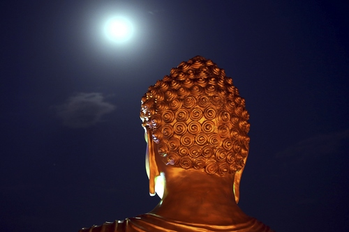 A full moon is seen behind a Buddha statue lit up on the eve of Buddha Jayanti festival at a monastery in Bhopal, India, Tuesday, May 13, 2014. The festival marks Buddha's birth, enlightenment and death. (AP Photo/ Rajeev Gupta)