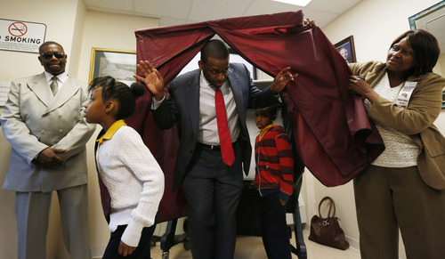 Newark mayoral candidate Shavar Jeffries, center, walks out of a voting booth with his children, Naomi Jeffries, 7, left, and Kaleb Jeffries, 9, after casting his vote, Tuesday, May 13, 2014, in Newark, N.J. The election will decide whether Jeffries, a former state assistant attorney general, or his opponent, City Councilman Ras Baraka, will take over the seat Cory Booker occupied from 2006 until October 2013, when he won a special election to succeed U.S. Sen. Frank Lautenberg, who died in office. (AP Photo)