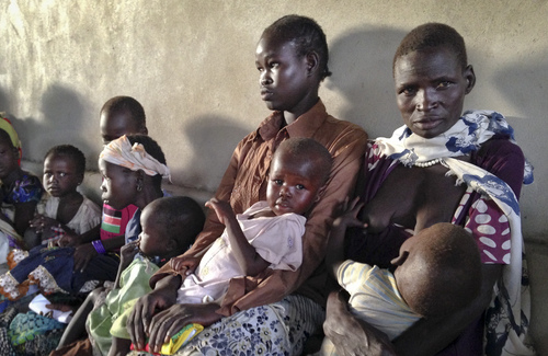 In this photo taken Friday, May 9, 2014 and made available Tuesday, May, 13, 2014, women and children wait to be treated at a hospital run by Medecins Sans Frontieres (Doctors Without Borders) in Leer, in oil-rich Unity State, South Sudan. Bodies stuffed in wells. Houses burned down. Children playing on military hardware. And young infants showing the skeletal outlines of severe hunger.  These are the scenes from a remote part of South Sudan _ Leer _ where the aid group Doctors Without Borders has just begun feeding severely malnourished children about three months after the group's hospital was destroyed in violence that has been ripping apart the country since December. (AP Photo/Josphat Kasire)