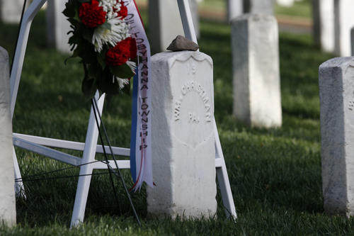 A stone of remembrance sits on the gravestone of Army Pvt. William Christman, who was the first military burial at the cemetery, marking the beginning of commemorations of the 150th anniversary of Arlington National Cemetery in Arlington, Va., Tuesday, May 13, 2014. The stone is from the original Christman home that still stands in Pocono Lake, Pennsylvania. Christman, 20, enlisted in the 67th Pennsylvania Infantry and was hospitalized for measles five weeks later, dying on May 11, 1864 and buried at Arlington on May 13. (AP Photo)
