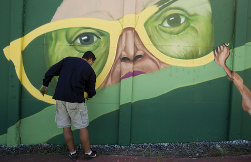 A street artist paints a section of a long wall along Radial Leste Avenue that is being covered with murals by Brazilian artists near the Itaquerao stadium which will host the World Cup's opening match in Sao Paulo, Brazil, Tuesday, May 13, 2014. The international soccer tournament starts June 12. (AP Photo/Andre Penner)