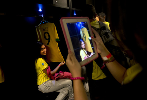 A student poses for a photo next to the jersey of soccer player Fred in the dressing room during a tour of Maracana stadium which will host World Cup matches in Rio de Janeiro, Brazil, Tuesday, May 13, 2014. The international soccer tournament will be the first in the South American nation since 1950. (AP Photo/Silvia Izquierdo)