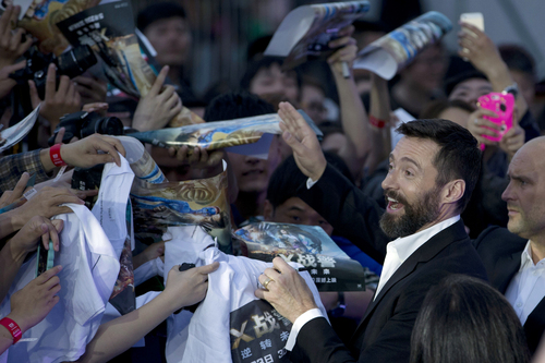 """Australian actor Hugh Jackman signs autographs for fans during the red carpet for his latest movie """"X-Men:Days of Future Past"""" in Beijing, China, Tuesday, May 13, 2014. Jackman said Tuesday he wasn't ready to give up his 14-year role as the X-Men character Wolverine as he visited China to promote the franchise's latest movie, which has local elements intended to appeal to the massive Chinese audience. (AP Photo/Ng Han Guan)"""