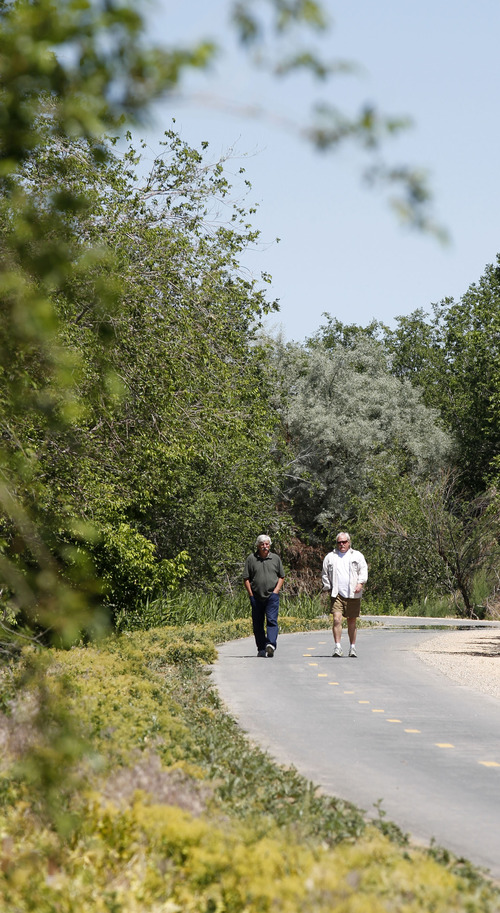 Al Hartmann  |  The Salt Lake Tribune  Walkers stroll along a newly opened section of the Jordan River Parkway Trail, running from about 1800 North in Salt Lake City to the Davis County line. The trail connects to the Legacy Parkway Trail.