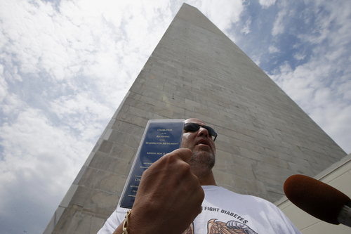 Marc Tanner, from Boca Raton, Fla., who was in the first group of tourists to visit the newly reopened Washington Monument, holds up a commemorative ticket to celebrate its re-opening, as he is interviewed by reporters after emerging from the monument, Monday, May 12, 2014, in Washington. The monument, which sustained damage from an earthquake in August 2011, reopened to the public today. (AP Photo)