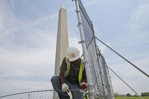 In this Friday, May 9, 2014 photo, worker Julio Dichis removes the fencing which closed the Washington Monument off to the public during renovations, in Washington. The monument, which sustained damage from an earthquake in August 2011, will re-open to the public on Monday, May 12, 2014. (AP Photo/Charles Dharapak)