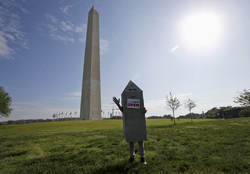 Steven Avila, a Department of Interior employee, wears a Washington Monument costume as he waves at photographers at the Washington Monument in Washington, Monday, May 12, 2104, ahead of a ceremony to celebrate its re-opening. The monument, which sustained damage from an earthquake in August 2011, is reopening to the public today. Avila made the costume to show his support for the re-opening of the monument. (AP Photo)